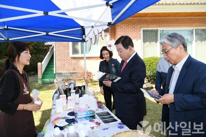 황선봉 군수(사진 가운데)와 이경진 예산군행복마을지원센터장(사진 오른쪽)이 부스를 살펴보는 모습.jpg
